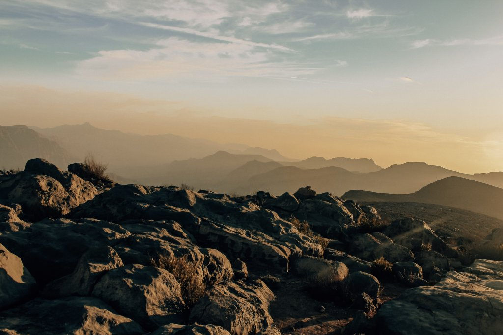 Rows of mountains on the way to Jebel Harim, under a pink and blue sunset.