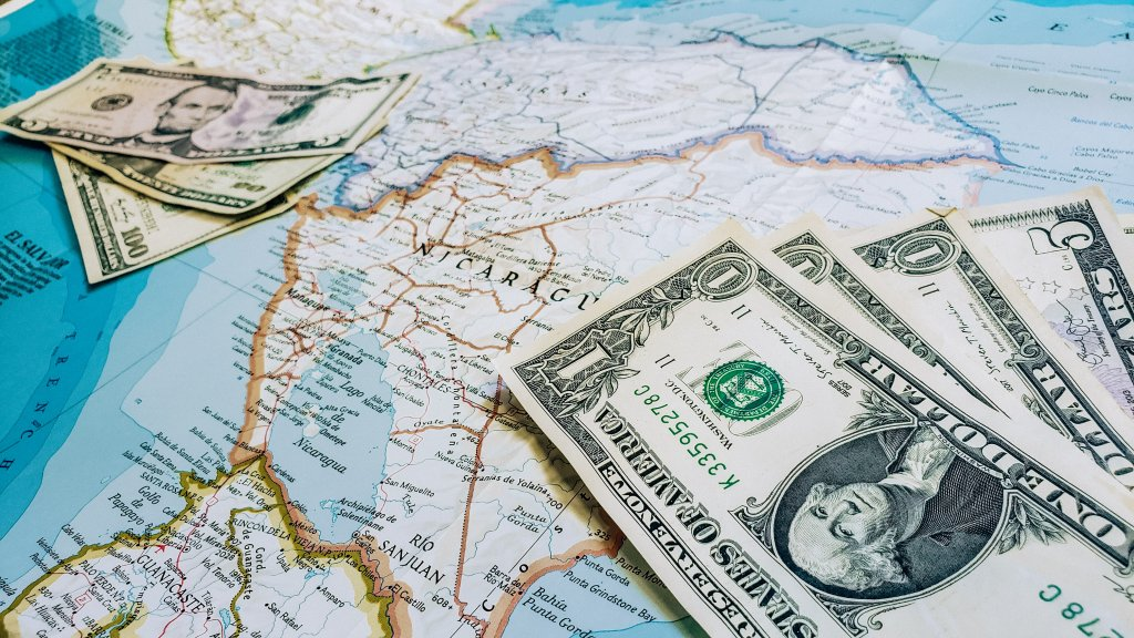 A map with money on it, symbolizing saving to travel (one of the simple bucket list ideas).
