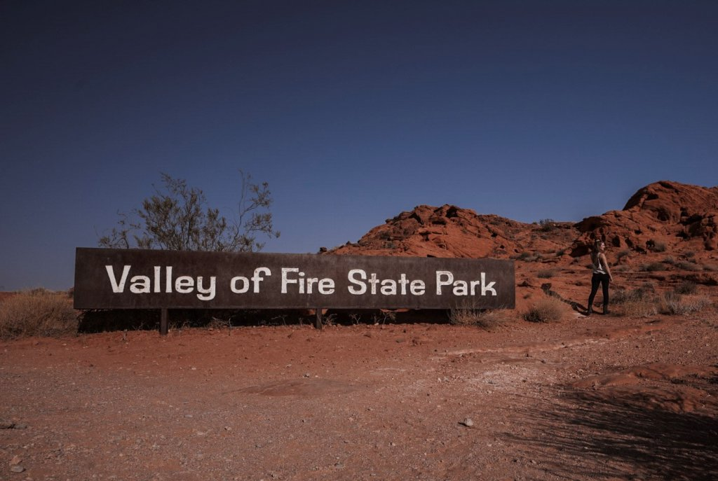 Monica next to the Valley of Fire State Park sign.