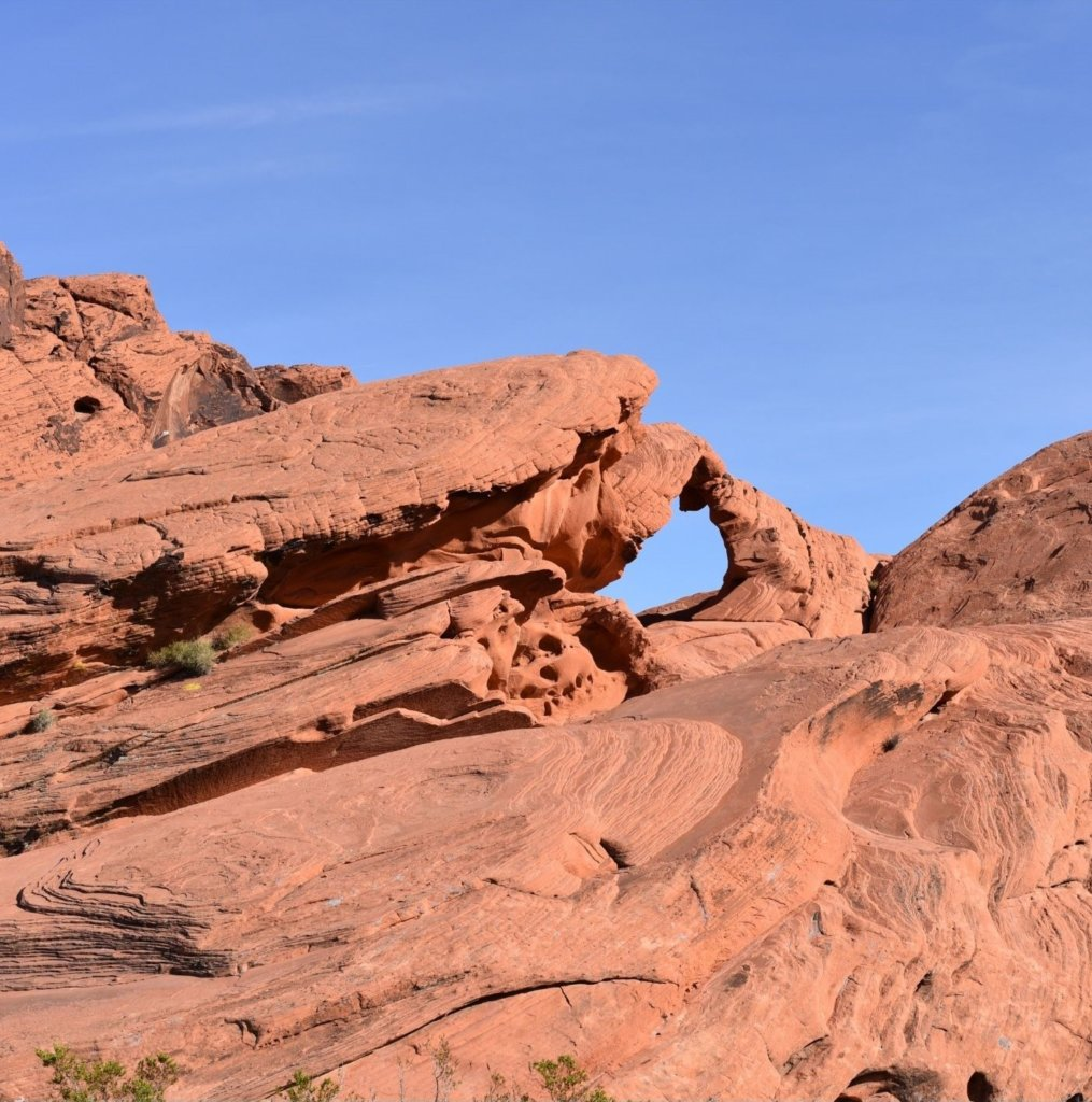 Valley of Fire State Park Arch Rock in front of blue sky.