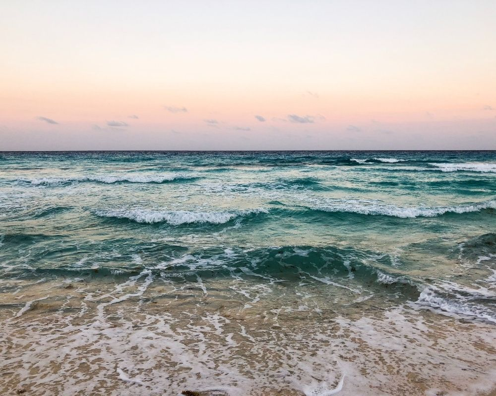 A pink sunset over the beach in Cancun.