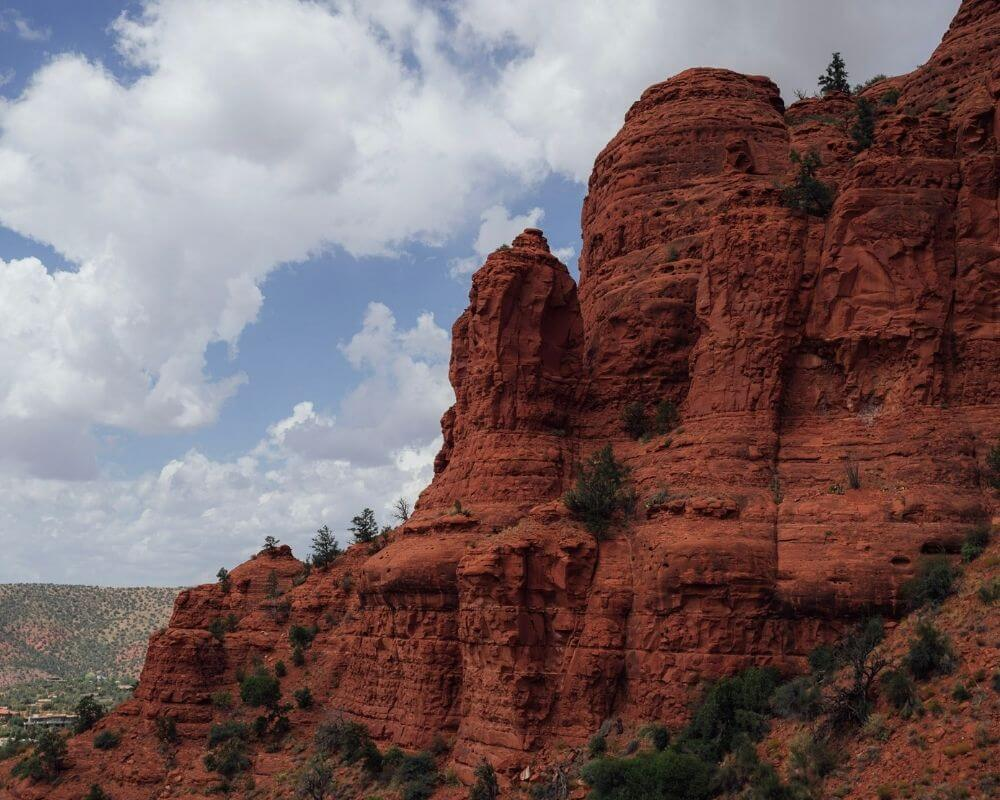 The red mountains of Sedona in front of cloudy skies.