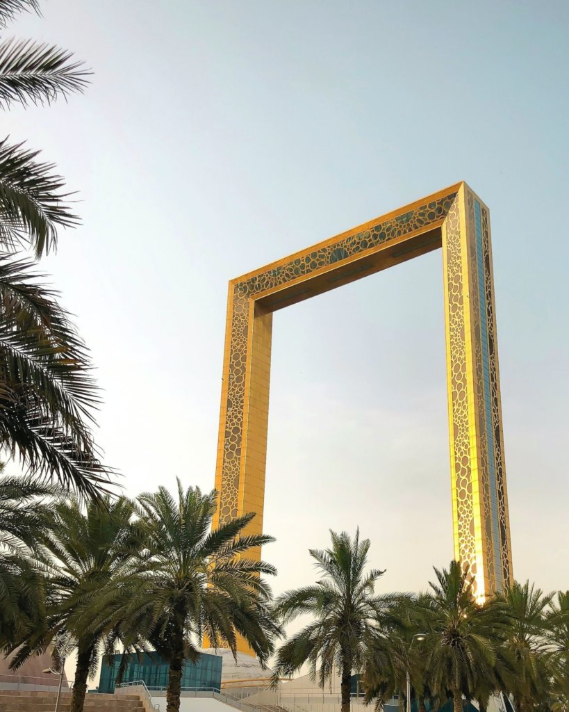 The Golden Frame in Dubai with green palm trees.