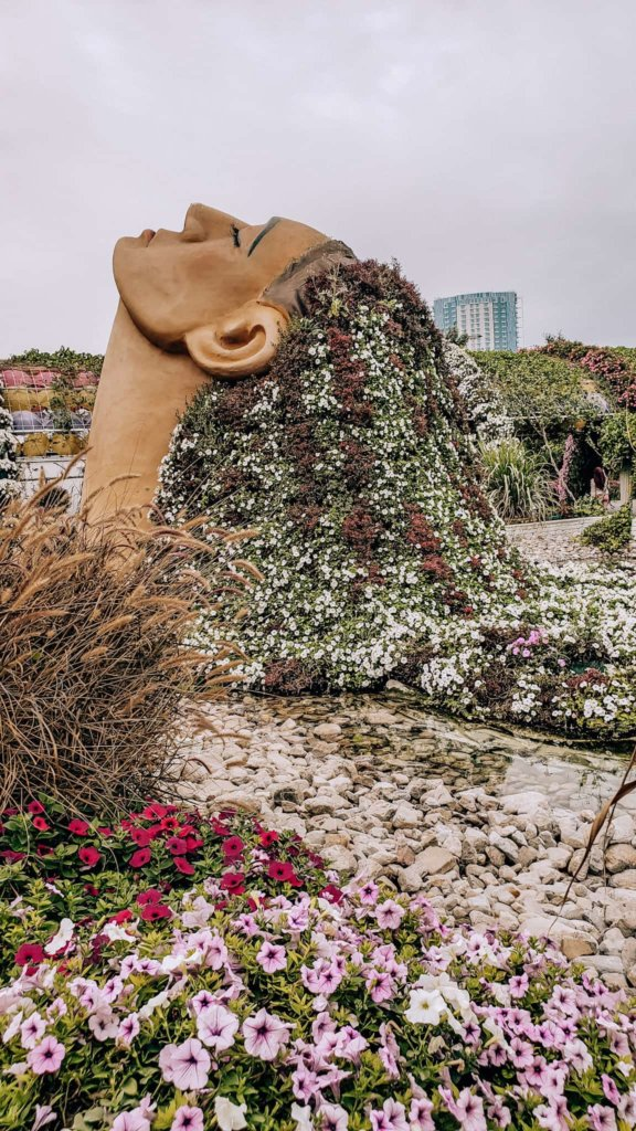 A sculpture featuring flowers in a woman's hair at the Dubai Miracle Garden.