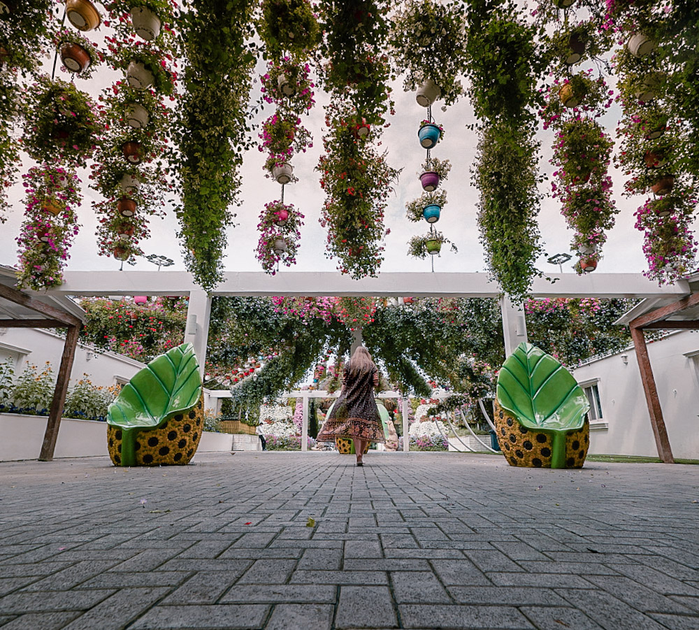 Monica walking under green foliage at the Dubai Miracle Garden.