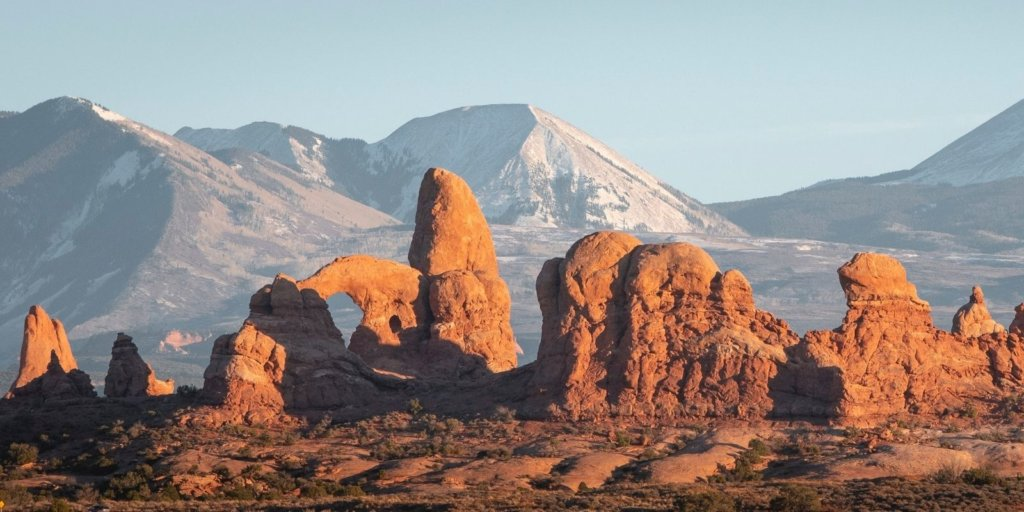 One of the most stunning views - rocks in front of mountains in front of blue sky in Arches National Park.
