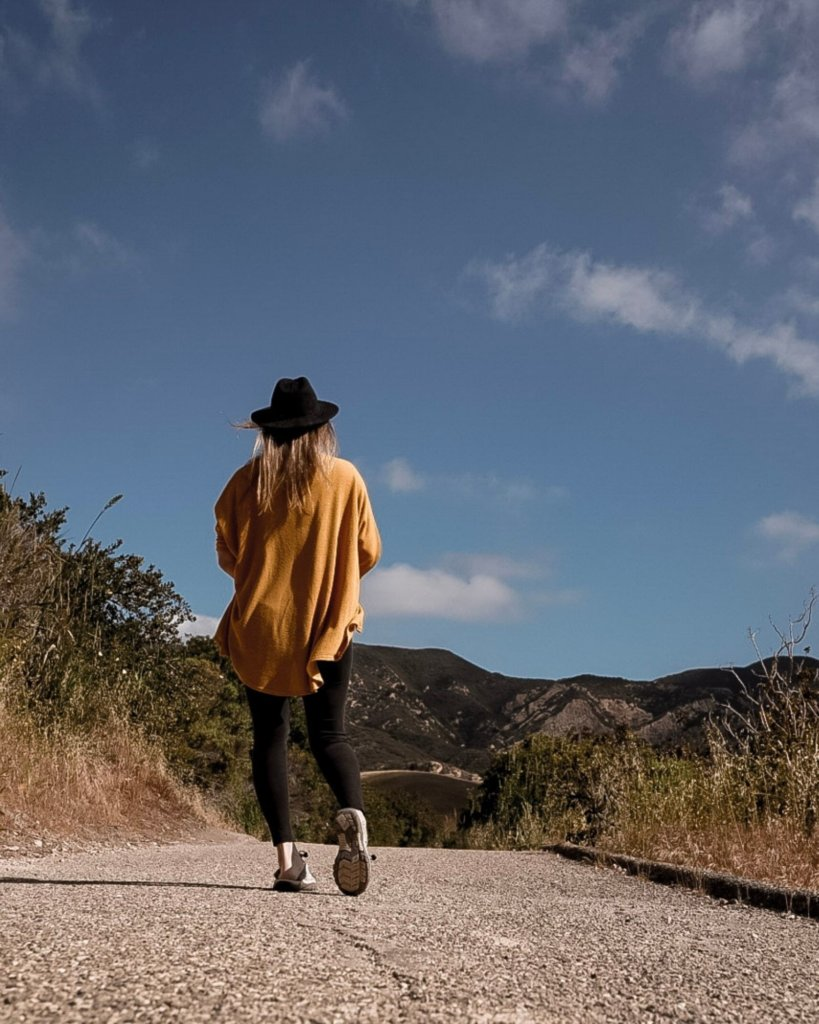 Monica walking the paved path to The Gaviota Wind Caves Trail.