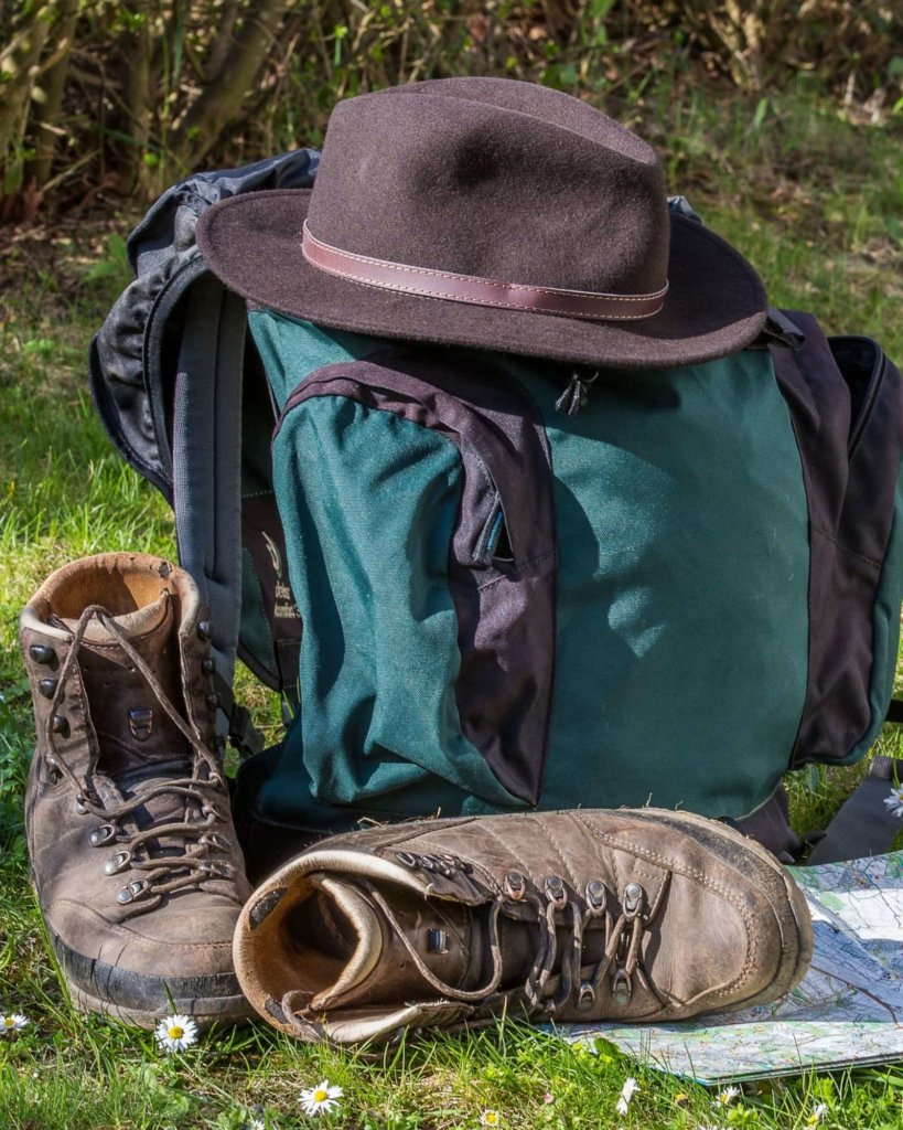 Backpack, hiking boots, and hat - Carry On Only Travel Tips.