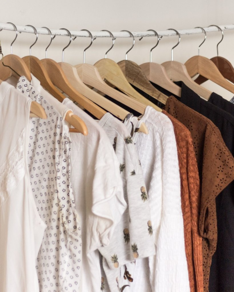 Neutral clothing on hangers - Carry On Only Travel Tips.